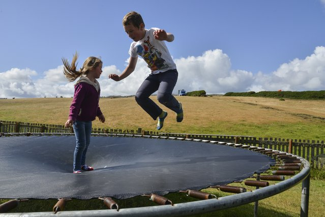 Anna Lee, L, and brother George Lee jump on the family trampoline in the back yard on Sunday, February 14, 2016, in Port Howard, Falkland Islands. (Photo by Jahi Chikwendiu/The Washington Post)