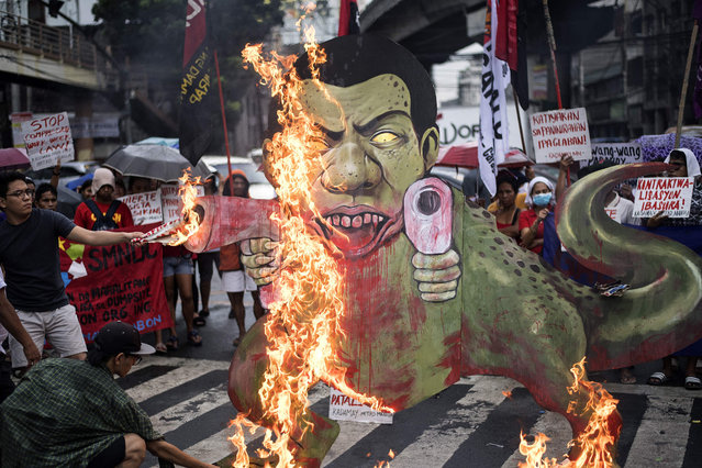 """Activists burn a caricature of Philippine President Rodrigo Duterte as a gun- toting tyrannosaurus dinosaur in Mendiola, near the Malacanang palace in Manila on December 8, 2017. The demonstrators denounced the government' s war on drugs campaign, the extension of martial law in Mindanao and the crackdown on activists, while calling for Duterte' s ouster from office. Philippine President Rodrigo Duterte on December 5 told human rights groups criticising his deadly anti- drug war to """"go to hell"""" after ordering police back to the frontlines of the crackdown. (Photo by Noel Celis/AFP Photo)"""