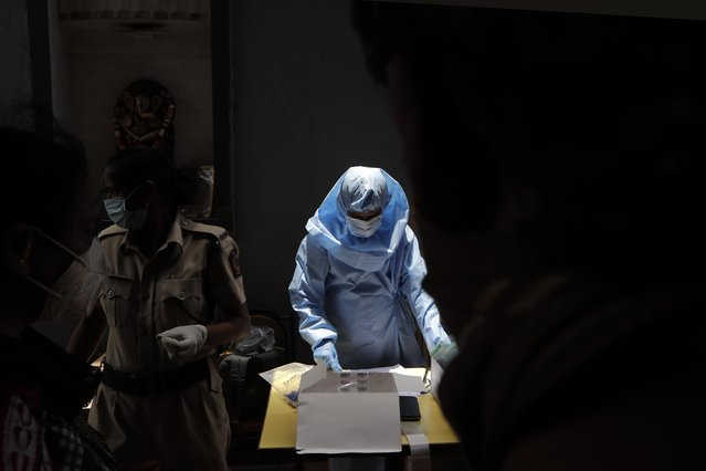 A health worker collects the samples of Covid 19 test at medical camp in Mumbai, India, Saturday, July 25, 2020. India is the third hardest-hit country by the pandemic in the world after the United States and Brazil. (Photo by Rajanish Kakade/AP Photo)