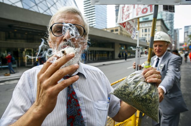 Activist Ray Turmel holds a bag of medical marijuana while he smokes a marijuana cigarette, as he calls for the total legalization of marijuana, outside the building where the federal election Munk Debate on Canada's Foreign Policy is being held in Toronto, Canada, September 28, 2015. (Photo by Mark Blinch/Reuters)