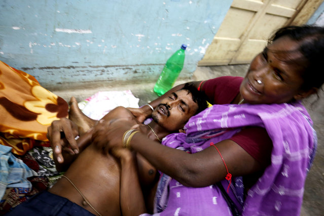 Sandha Mal (R) tries to help her son Lalu Mal who reacts with stomach pain at a hospital in Tamluk, some 115 km west  of Calcutta, India, 28 September 2015 after the victim drank poisonous liquor. At least 12 people have died and some 50 were admitted to hospitals after consuming illegal alcohol in eastern India, police said. Villagers in West Bengal state's Midnapore district fell ill after drinking the alcohol on the weekend. (Photo by Piyal Adhikary/EPA)