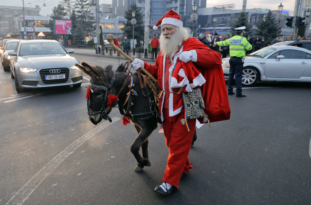 A man wearing a Santa Claus outfit walks with a donkey in Piatra Neamt, northern Romania, Thursday, December 28, 2017. A parade of new year's traditions took place in the city. (Photo by Vadim Ghirda/AP Photo)