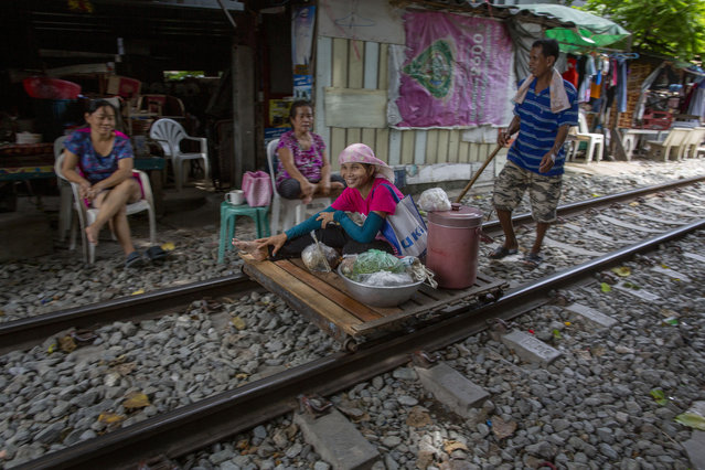 A vendor pushes an improvised cart with a woman and merchandise along a rarely used rail track in Bangkok, Thailand, Thursday, June 25, 2020. Daily life in the capital slowly returns to normal as the Thai government eases many restrictions imposed weeks ago to combat the spread of COVID-19. Though emergency regulations require the use of face masks in public, some residents have become apathetic as Thailand has record zero local transmission for over three weeks. (Photo by Gemunu Amarasinghe/AP Photo)