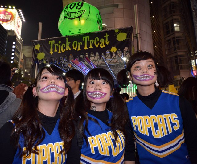 People wear costumes as they pose for pictures while taking part in a Halloween parade in Tokyo on October 31, 2014. Tens of thousands of people gathered at Tokyo's Shibuya fashion district to celebrate Halloween. (Photo by Yoshikazu Tsuno/AFP Photo)