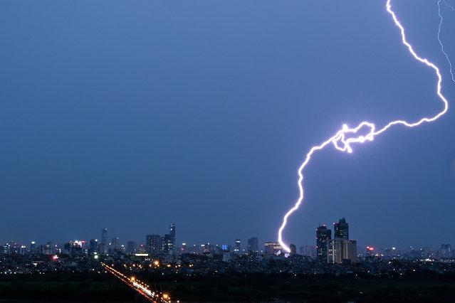 Lightning strikes over the Hanoi skyline on May 13, 2020. (Photo by Manan Vatsyayana/AFP Photo)