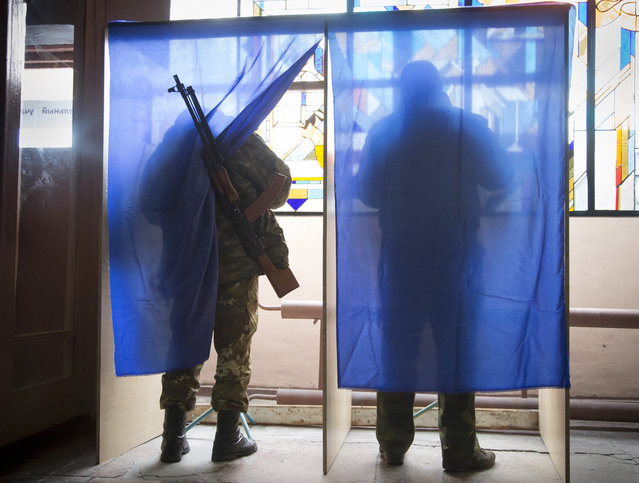 Pro-Russian rebels fill their ballots in voting cabins at a polling station set up inside a rebel military base during rebel elections in the city of Donetsk, eastern Ukraine Sunday, November 2, 2014. The pro-Russian rebels are holding the elections that were dismissed by Ukraine and the West as illegitimate. (Photo by Dmitry Lovetsky/AP Photo)