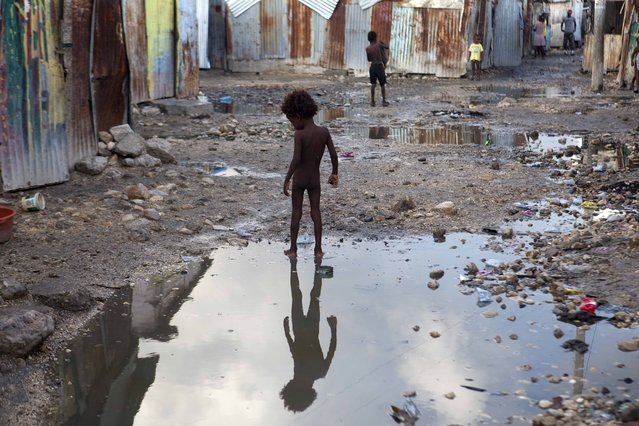 A child plays in a puddle in the seaside slum of Port-au-Prince, Haiti, Wednesday, September 6, 2017. (Photo by Dieu Nalio Chery/AP Photo)