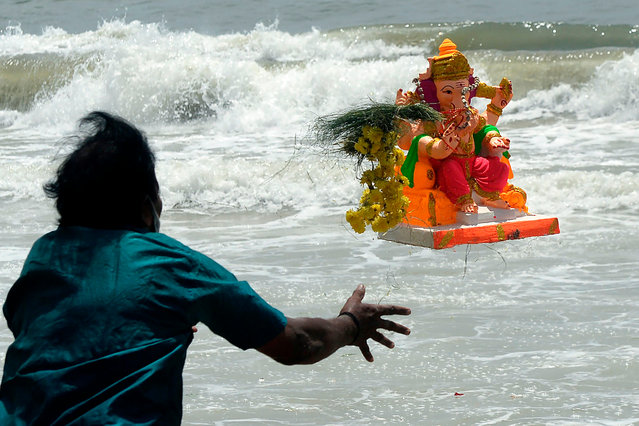 A devotee throws a clay idol of Hindu elephant-headed deity Ganesh into the sea on the third day of the Ganesh Chaturthi festival, in Chennai on August 24, 2020. (Photo by Arun Sankar/AFP Photo)