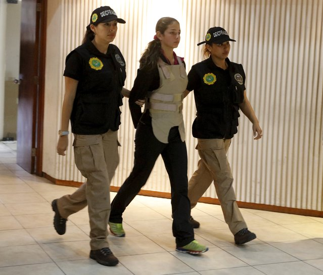 Police officers escort Italian citizen Isabel Mendoza Poma (C), who was arrested during a police seizure of counterfeit U.S. dollar bills, at a news conference in Lima October 14, 2015. The National Police seized $836,000 in fake bills that had been packed in bags and backpacks  destined for the city of New York in the United States, according to a police media release. (Photo by Guadalupe Pardo/Reuters)