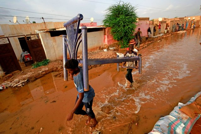 Sudanese youth carry a bed frame as they make their way through a flooded street in alqamayir area in the capital's twin city of Omdurman, on August 26, 2020. (Photo by Ashraf Shazly/AFP Photo)
