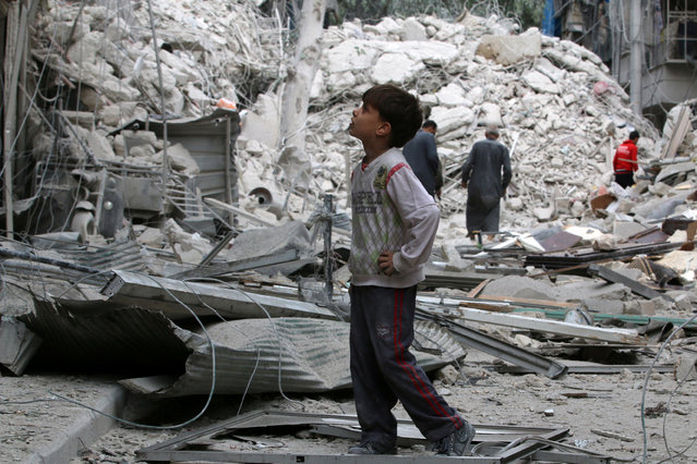 A boy inspects a damaged site after airstrikes on the rebel held Tariq al-Bab neighbourhood of Aleppo, Syria September 23, 2016. (Photo by Abdalrhman Ismail/Reuters)