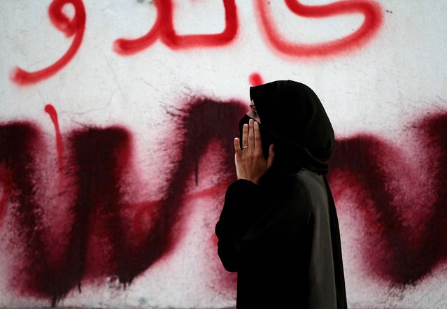 An anti-government protester standing in front of graffiti that has been partly painted over shouts toward police during clashes in Manama, Bahrain, March 2, 2013. Protesters tried to march on the country's heavily guarded main public hospital, saying they intended to retrieve the body of a protester who died last week. The body of Mahmoud al-Jazeeri, 20, has not yet been released for burial because of a dispute between the family and the government over funeral plans. (Photo by Hasan Jamali/Associated Press)