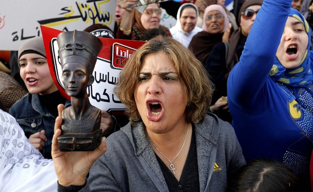 A woman raises a statue of pharaonic Queen Hatshepsut as she shouts slogans during a demonstration in Cairo marking International Women's Day. (Photo by Amr Nabil/Associated Press)