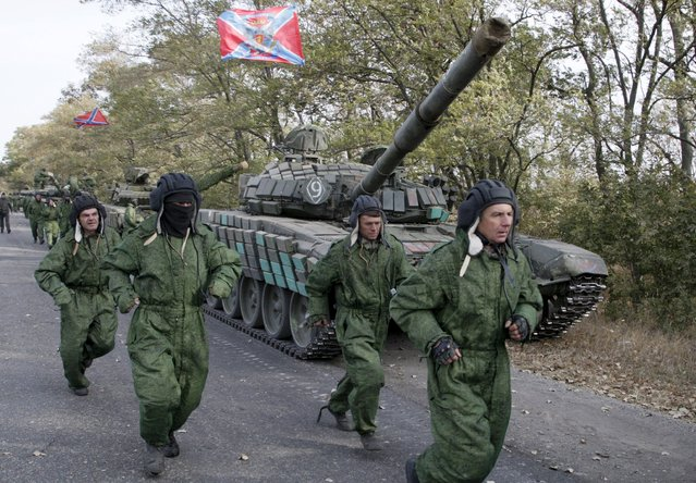 Crew members run before driving the tanks of the self-proclaimed Donetsk People's Republic forces during a withdrawal from the frontline near the town of Novoazovsk in Donetsk region, Ukraine, October 21, 2015. (Photo by Alexander Ermochenko/Reuters)