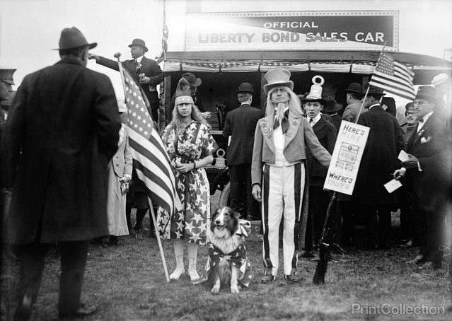 "Liberty Loans, Liberty Bond Sales Car, John N. Stevenson as ""Uncle Sam"" and Girl in Star-Spangled Dress with Star-Spangled Dog. Photographed by Harris & Ewing in 1918 on 5 x 7 in. glass plate negative. Sign reads ""Hear's Mine Where's Yours?"""