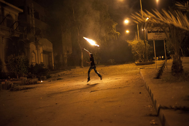 An Egyptian protester attacks the Muslim Brotherhood headquarters in the Muqattam district in Cairo, Sunday, June 30, 2013. (Photo by Manu Brabo/AP Photo)