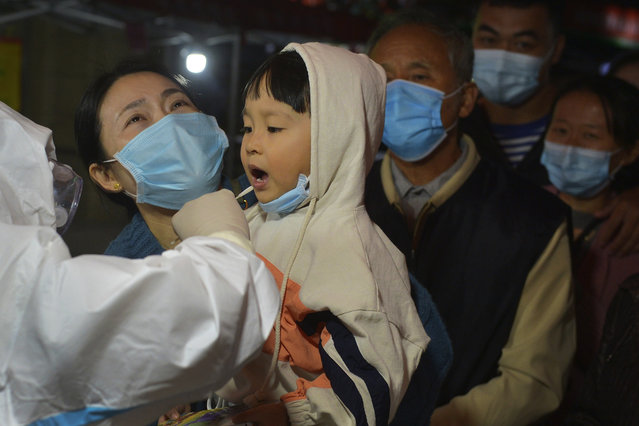 A medical staff takes a swab from a child as residents wearing face masks to help curb the spread of the coronavirus line up for the COVID-19 test near the residential area in Qingdao in east China's Shandong province on Monday, October 12, 2020. Authorities in the eastern Chinese port city of Qingdao said Tuesday that they have completed coronavirus tests on more than 3 million people following the country's first reported local outbreak of the virus in nearly two months. (Photo by Chinatopix via AP Photo)