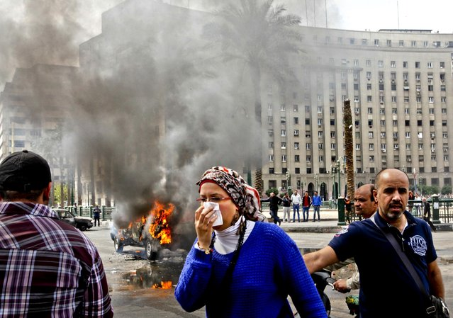 A woman covers her face as she passes by a burning police car, that set on fire by angry protesters in Tahrir Square during a rally against former President Mubarak, in Cairo, Egypt, on March 18, 2013. (Photo by Amr Nabil/Associated Press)