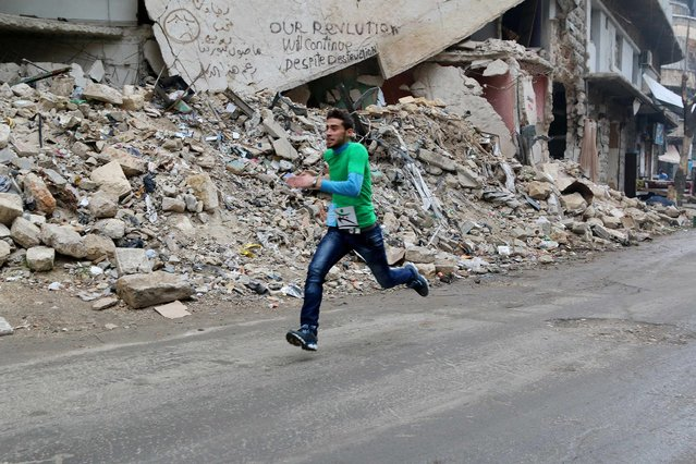 A participant runs past a damaged building as he competes in a running race along a street in Aleppo's Bustan al-Qasr neighborhood, a rebel-controlled area, December 2, 2014. (Photo by Mahmoud Hebbo/Reuters)