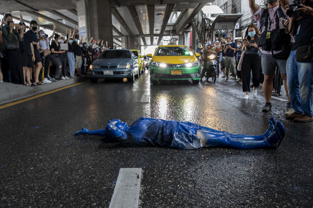 A pro-democracy protester covered in blue paint lies on a road during a protest in Udom Suk, suburbs of Bangkok, Thailand, Saturday, October 17, 2020. The authorities in Bangkok shut down mass transit systems and set up roadblocks Saturday as Thailand's capital faced a fourth straight day of determined anti-government protests. (Photo by Gemunu Amarasinghe/AP Photo)