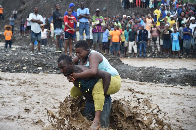 A man carries a woman across a  river at Petit Goave where a bridge collapsed during the rains of the Hurricane Matthew, southwest of Port-au-Prince, October 5, 2016. (Photo by Hector Retamal/AFP Photo)