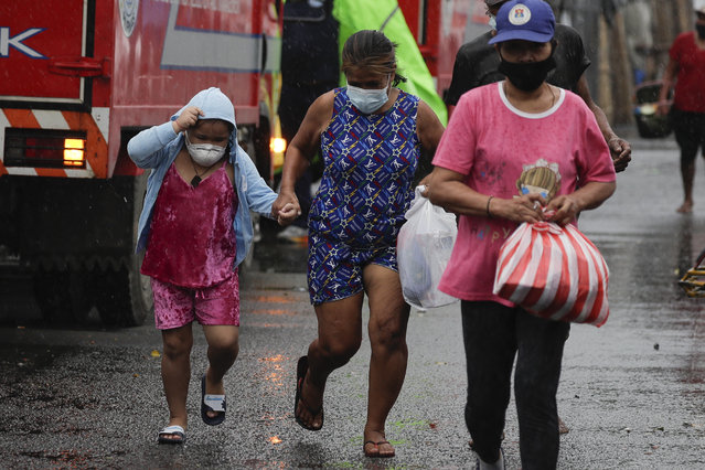 Residents wearing a face mask to prevent the spread of the coronavirus run back to their home as rains from a typhoon locally known as Goni starts in Manila, Philippines on Sunday November 1, 2020. The super typhoon slammed into the eastern Philippines with ferocious winds early Sunday and about a million people have been evacuated in its projected path, including in the capital where the main international airport was ordered closed. (Photo by Aaron Favila/AP Photo)