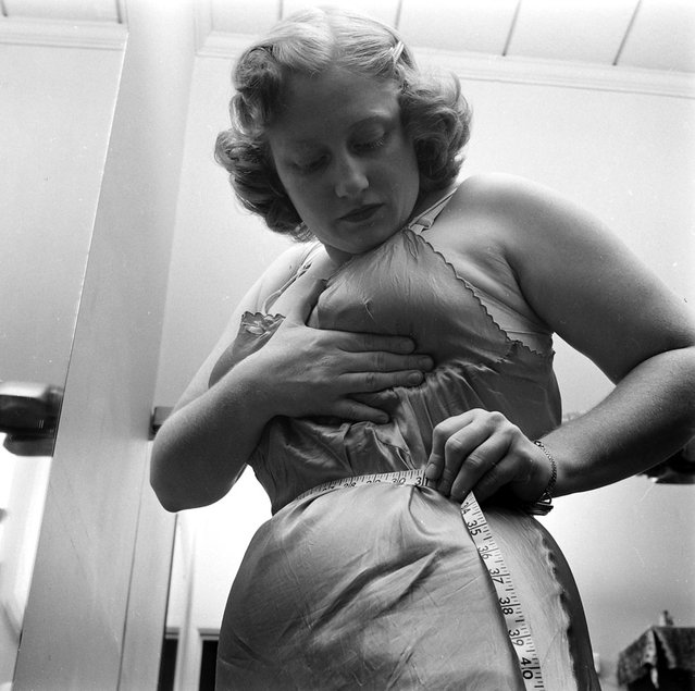 Dorothy Bradley, photographed for LIFE magazine article on obesity, measures her waist, 1949. (Photo by Martha Holmes/Time & Life Pictures)
