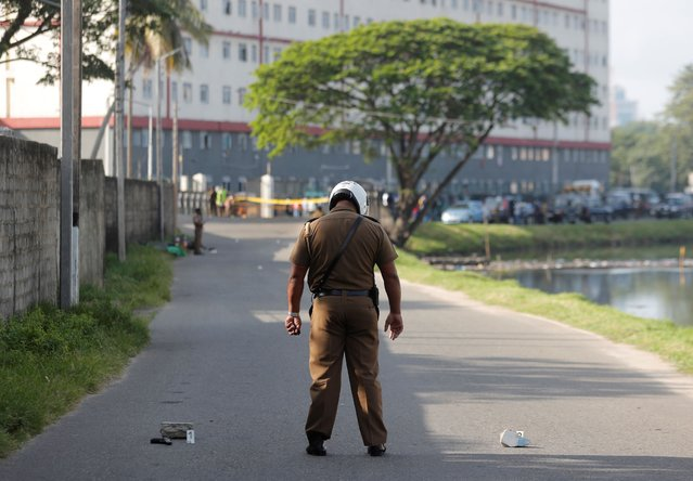 A Sri Lankan police officer stands at a crime scene following a shoot out between police officers and drug traffickers in Colombo, Sri Lanka, Tuesday, October 20, 2020. (Photo by Eranga Jayawardena/AP Photo)