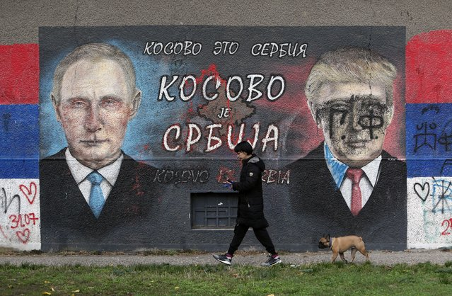 """A woman with a dog passes by graffiti depicting the Russian President Vladimir Putin, left, and U.S. President Donald Trump vandalized with paint in a suburb of Belgrade, Serbia, Tuesday, November 3, 2020. The Cyrillic letters on graffiti read """"Kosovo is Serbia"""". For some Serbian leaders, U.S. President Donald Trump is a hero while his challenger Joe Biden is nothing but a """"Serb hater"""". So, there is no surprise that Serbs living in the U.S. were called on to vote for Trump in Tuesday's election nor that Serbia's populist president said his victory would be better for the country. (Photo by Darko Vojinovic/AP Photo)"""
