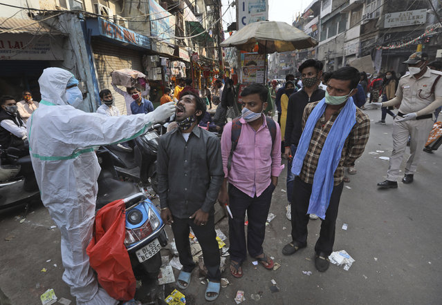 A health worker takes a sample to test for COVID-19 test at a market place in New Delhi, India, Thursday, November 19, 2020. India's confirmed coronavirus caseload is expected to surpass 9 million on Friday as authorities in New Delhi battle to slow down the surge of infections in the city by increasing testing. The country's overall tally of confirmed cases is currently the second largest in the world behind the United States. (Photo by Manish Swarup/AP Photo)
