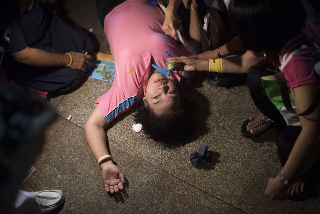 A woman passes out after the official statement announcing the death of Thailand's King Bhumibol Adulyadej on October 13, 2016 in Bangkok, Thailand. King Bhumibol, the world's longest reigning monarch, died at 88 in Bangkok's Siriraj Hospital on Thursday. (Photo by Borja Sanchez Trillo/Getty Images)