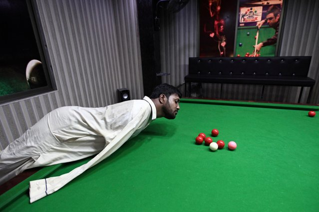Muhammad Ikram, 32, who was born without arms, plays snooker with his chin at a local club in Samundri, Pakistan, October 20, 2020. (Photo by Mohsin Raza/Reuters)