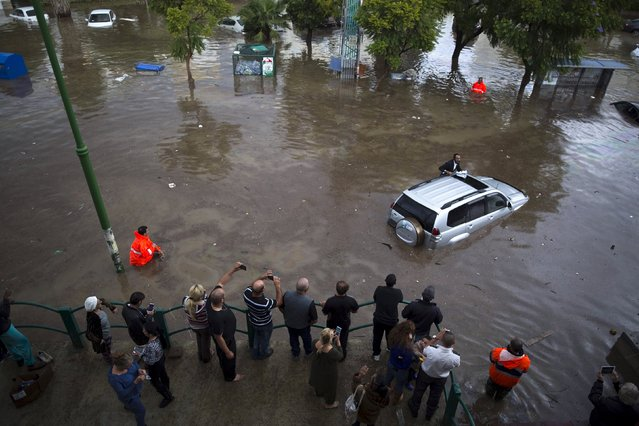 Onlookers watch as a motorist climbs out of his vehicle after getting stuck on a flooded street in the southern city of Ashkelon, Israel, November 9, 2015. (Photo by Amir Cohen/Reuters)
