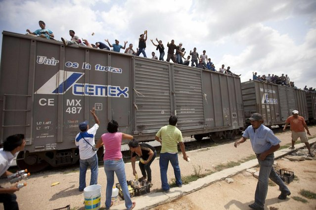 Residents toss food to migrants riding on top of a northern bound train toward the US-Mexico border, in Union Hidalgo, southern Mexico, Monday, April 29, 2013. Migrants crossing Mexico to get to the U.S. have increasingly become targets of criminal gangs who kidnap them to obtain ransom money. (Photo by Eduardo Verdugo/AP Photo)