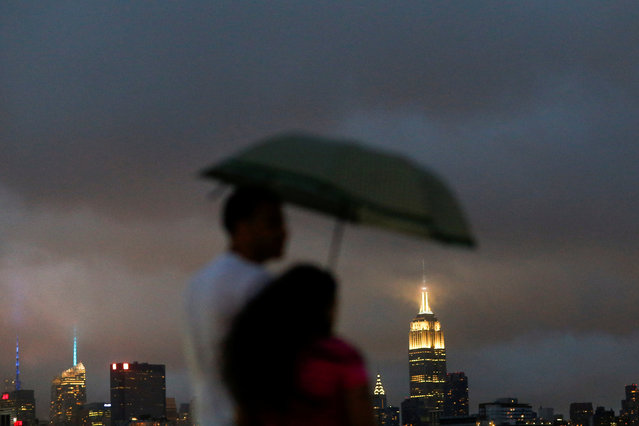 People cover from rain as a low level cloud formation hovers over New York's Empire State Building and the skyline of midtown Manhattan as seen across the Hudson River in Hoboken, New Jersey, U.S., August 21, 2016. (Photo by Eduardo Munoz/Reuters)
