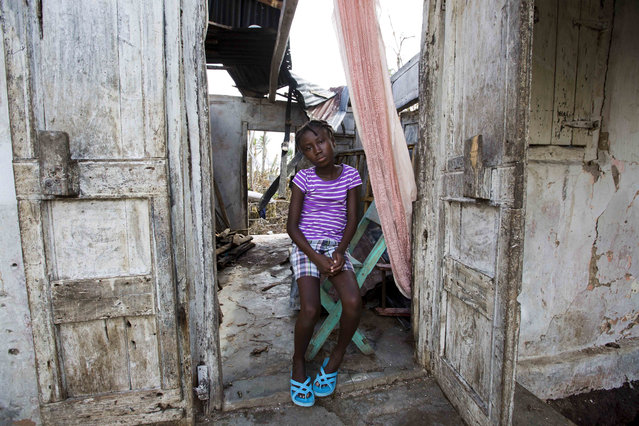 """Love Manie Simeus, 12, sits in what's left of her grandmother's home in the village of Mersan, located in Camp-Perrin, a district of Les Cayes, Haiti, October 17, 2016. When asked what she missed most from her old life, she said she longed for a plastic baby doll she named Natasha. Asked what happened to the doll, she burst out laughing and said: """"She's dead now. She got crushed by the roof"""". (Photo by Dieu Nalio Chery/AP Photo)"""