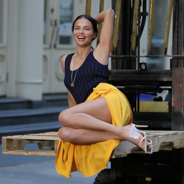 Supermodel Adriana Lima, wearing a ruffled yellow skirt and black tank top, poses on a forklift in Soho in New York City, New York on April 20, 2018. (Photo by Christopher Peterson/Splash News and Pictures)