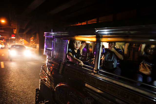 Passengers look from inside a passing jeepney at the site where a man was killed in a shootout with police in Manila, Philippines early October 21, 2016. (Photo by Damir Sagolj/Reuters)