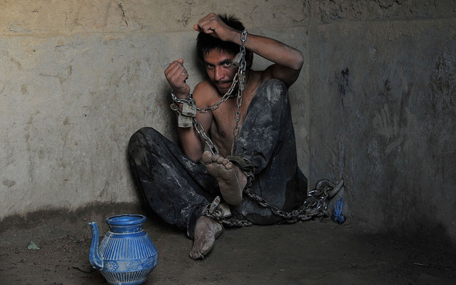 A mentally ill patient chained to a wall at the Mia Ali Baba holy shrine in the village of Samar Khel on the outskirts of Jalalabad, on May 16, 2013. At the Mia Ali Baba sanctuary the patients, presumed to be possessed by jinns (demons), are chained by the wrist inside, or in the open air to a tree, for 40 days. (Photo by Noorullah Shirzada/AFP Photo)