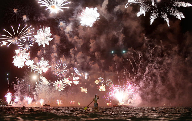 A man rides a stand up paddle board as fireworks explode above him during New Year's festivities on Copacabana Beach on January 1, 2015 in Rio de Janeiro, Brazil. Up to 2 million revelers were expected on Copacabana Beach to watch the annual New Year's fireworks display which this year coincided with the start of the city's 450th anniversary celebrations. (Photo by Mario Tama/Getty Images)