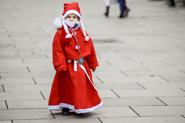 People dressed as Santa Claus take part in a charity event in Pristina on December 13, 2020 to raise funds for families in need in Kosovo, amid the COVID-19 outbreak, caused by the novel coronavirus. (Photo by Armend Nimani/AFP Photo)