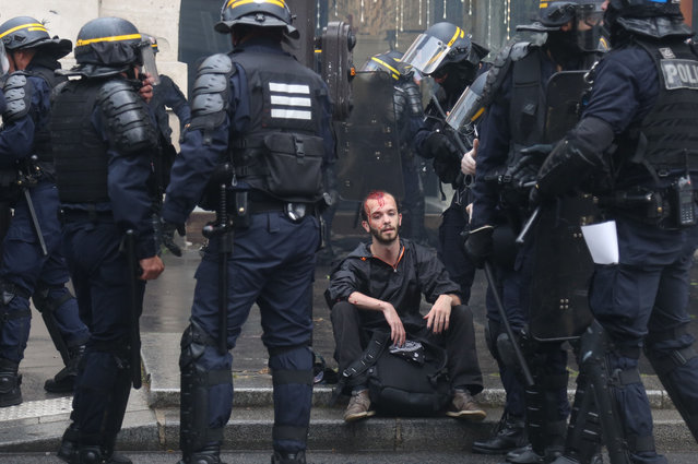 """A wounded demonstrator is surrounded by riot police officers, on May 22, 2018 in Paris, during a nationwide day protest by French public sector employees and public servants against the overhauls proposed by French President, calling them an """"attack"""" by the centrist leader against civil services as well as their economic security. (Photo by Zakaria Abdelkafi/AFP Photo)"""