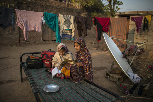 Girls study outside their house on the outskirts of Islamabad January 1, 2015. (Photo by Zohra Bensemra/Reuters)