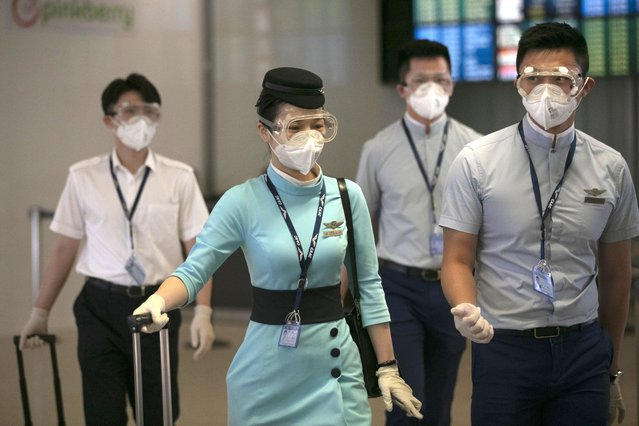 Flight attendants from Xiamen Airlines wear protective goggles and masks as they walk through the arrivals area at the Los Angeles International Airport Wednesday, June 24, 2020, in Los Angeles. The U.S. recorded a one-day total of 34,700 new COVID-19 cases, the highest in two months, according to the count kept by Johns Hopkins University. (AP Photo/Jae C. Hong)