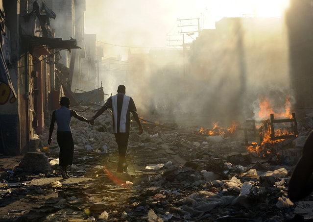 A couple holds hands as they walk through earthquake rubble and debris that was set on fire in Port-au-Prince, Haiti on January 18, 2010. (Photo by Carol Guzy/The Washington Post via Getty Images)