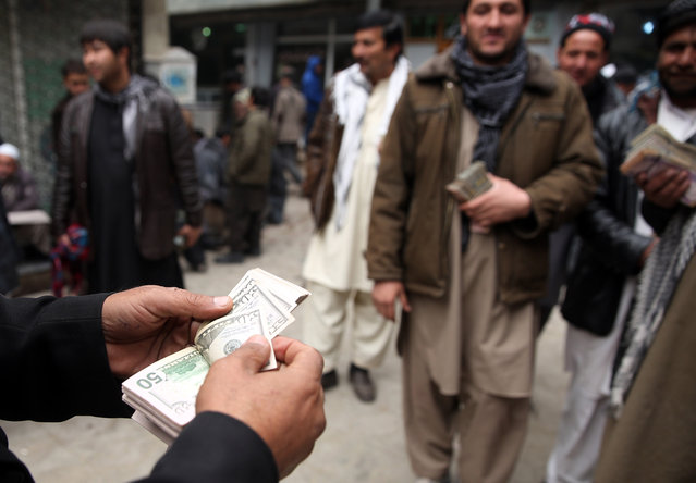 Afghan money changer, left, counts a pile of currency at the Money and Exchange Market in Kabul, Afghanistan, Monday, January 12, 2015. The Afghanistan's currenct, the Afghani, stands at 57.60 against the U.S. dollar. (Photo by Massoud Hossaini/AP Photo)