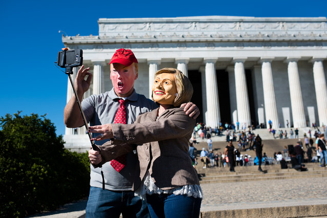 Ben Arnold, 36, left, and his wife Melissa Arnold, 34, of Marietta, Ohio came to Washington, DC to celebrate their tenth wedding anniversary on October 14, 2016. To celebrate, they have decided to take selfies of themselves at various tourist sites wearing Hillary and Donald masks and them post them to social media. They take a selfie in front of the Lincoln Memorial. They are Republicans and will be voting for Trump. They went to the goodwill the night before to buy a suit jacket and red tie. (Photo by Sarah L. Voisin/The Washington Post)