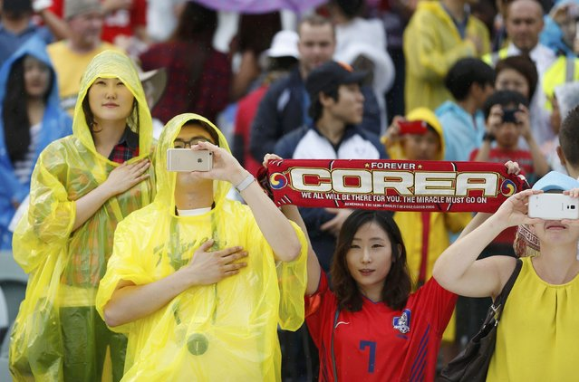 South Korea fans take photos as they await the start of the Asian Cup Group A soccer match betweeen Kuwait and South Korea at the Canberra stadium in Canberra January 13, 2015. (Photo by Tim Wimborne/Reuters)