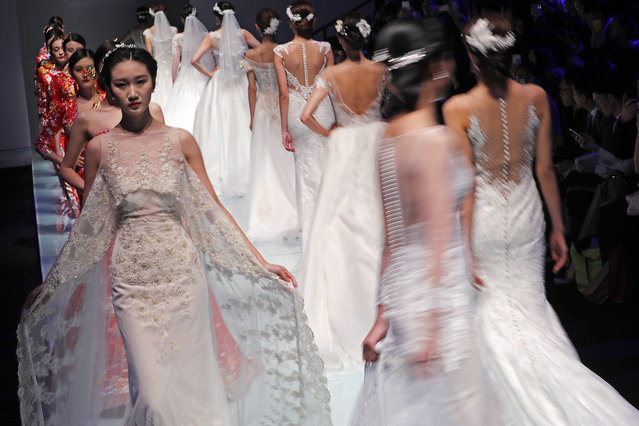 Models present wedding dresses created by Famory on stage during the Mercedes-Benz China Fashion Week in Beijing, Wednesday, October 26, 2016. (Photo by Andy Wong/AP Photo)