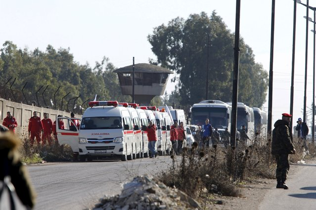 Syrian Red Crescent units wait in the district of Waer during a truce between the government and rebel fighters, in Homs December 9, 2015. Busloads of Syrians including rebel fighters left the last insurgent-held area of Homs on Wednesday under a rare local truce agreement in Syria's nearly five-year conflict that will shore up government control over the city. (Photo by Omar Sanadiki/Reuters)